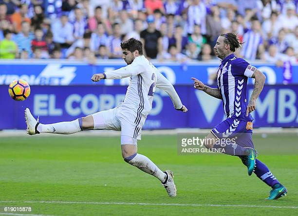 Real Madrid's forward Alvaro Borja Morata kicks the ball to score a goal next to Deportivo Alaves' defender Alexis Ruano during the Spanish league...