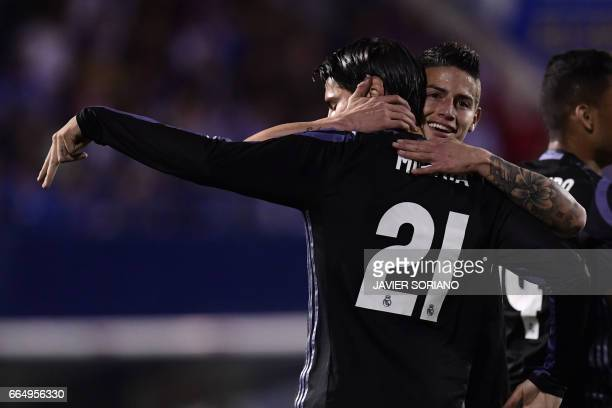 Real Madrid's forward Alvaro Morata celebrates with Real Madrid's Colombian midfielder James Rodriguez after scoring their second goal during the...