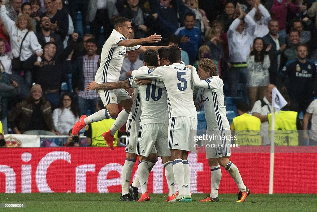 Real Madrid's forward Alvaro Morata (unseen) celebrates with teammates after scoring during the UEFA Champions League football match Real Madrid CF vs Sporting CP at the Santiago Bernabeu stadium in Madrid on September 14, 2016. / AFP / CURTO
