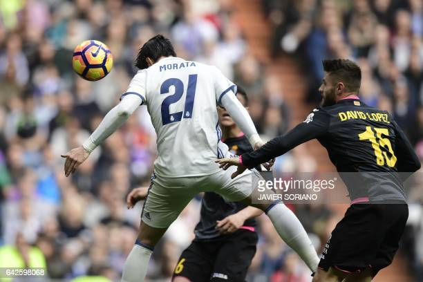 Real Madrid's forward Alvaro Morata heads the ball to score a goal beside Espanyol's defender David Lopez during the Spanish league football match...