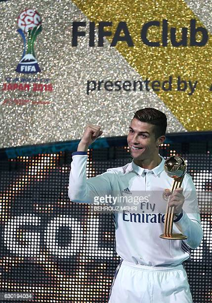 Real Madrid's forward Cristiano Ronaldo poses as he holds the Golden Ball trophy after winning the Club World Cup football final match between...