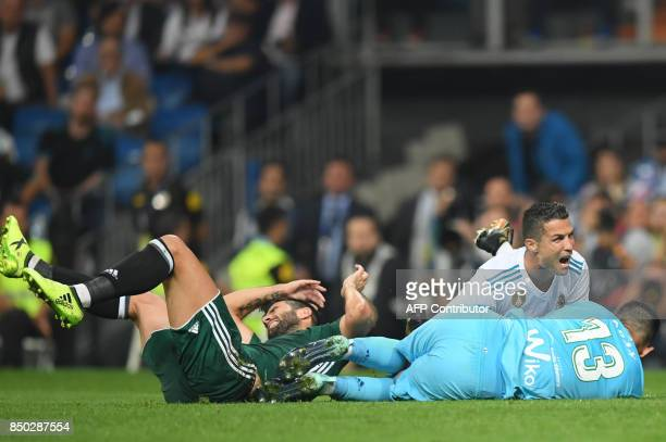 Real Madrid's forward from Portugal Cristiano Ronaldo falls down beside Real Betis' goalkeeper from Spain Antonio Adan during the Spanish league...