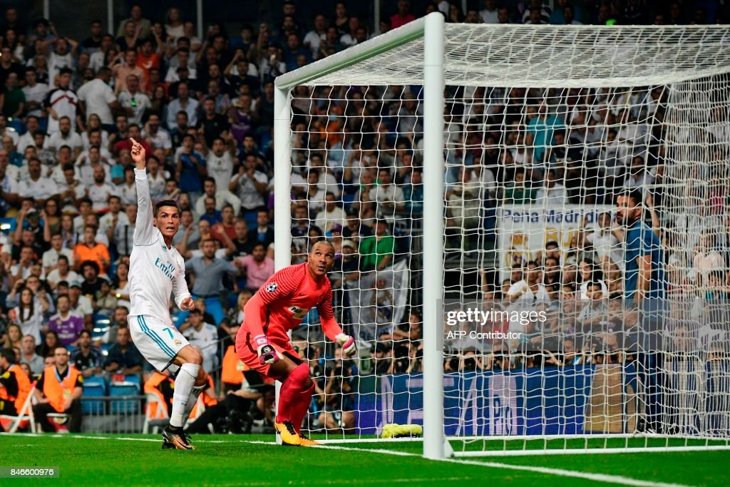TOPSHOT - Real Madrid's forward from Portugal Cristiano Ronaldo (L) gestures past APOEL Nicosia's goalkeeper from the Netherlands Boy Waterman after a cancelled goal during the UEFA Champions League football match Real Madrid CF vs APOEL FC at the Santiago Bernabeu stadium in Madrid on September 13, 2017. /