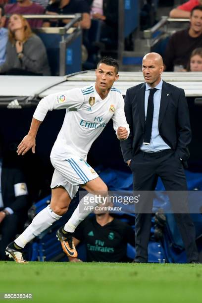 Real Madrid's forward from Portugal Cristiano Ronaldo runs in front of Real Madrid's French coach Zinedine Zidane during the Spanish league football...