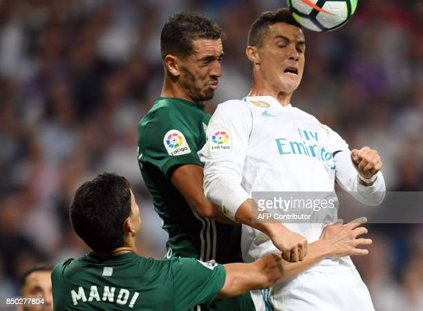 Real Madrid's forward from Portugal Cristiano Ronaldo vies with Real Betis' defender from Morocco Zou during the Spanish league football match Real...