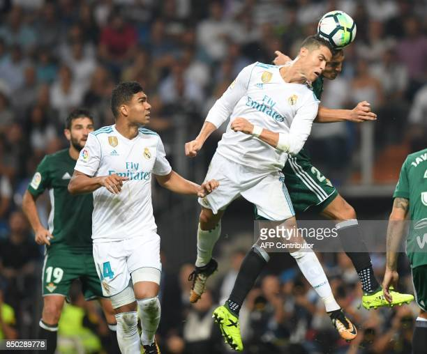 Real Madrid's forward from Portugal Cristiano Ronaldo vies with Real Betis' defender from Algeria Aissa Mandi beside Real Madrid's midfielder from...