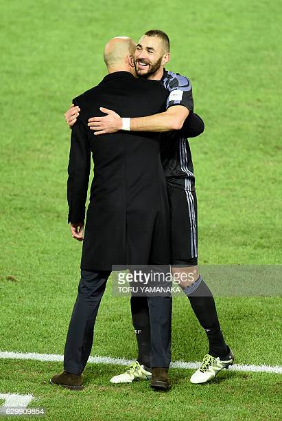 Real Madrid's forward Karim Benzema is congratulated by head coach Zinedine Zidane after scoring a goal during the Club World Cup semifinal football...