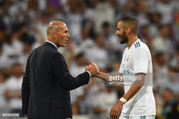 Real Madrid's French coach Zinedine Zidane and Real Madrid's French forward Karim Benzema congratulate each other as they celebrate their Supercup...