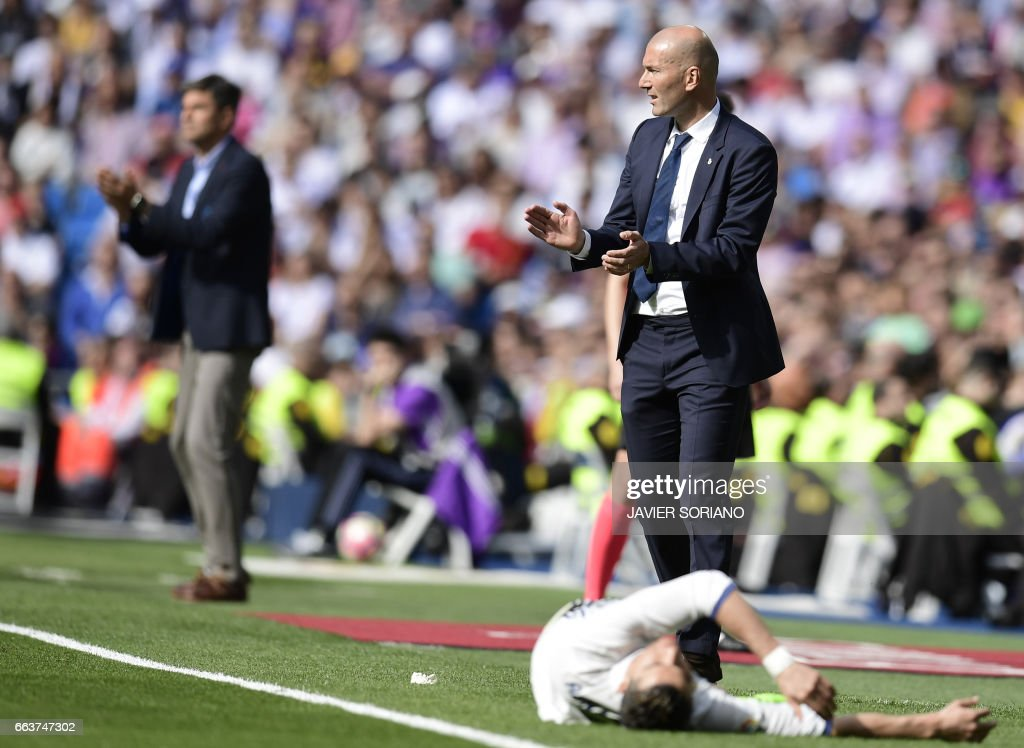 TOPSHOT - Real Madrid's French coach Zinedine Zidane (R) applauds as Real Madrid's Portuguese forward Cristiano Ronaldo lies in front of him during the Spanish league football match Real Madrid CF vs Deportivo Alaves at the Santiago Bernabeu stadium in Madrid on April 2, 2017. /