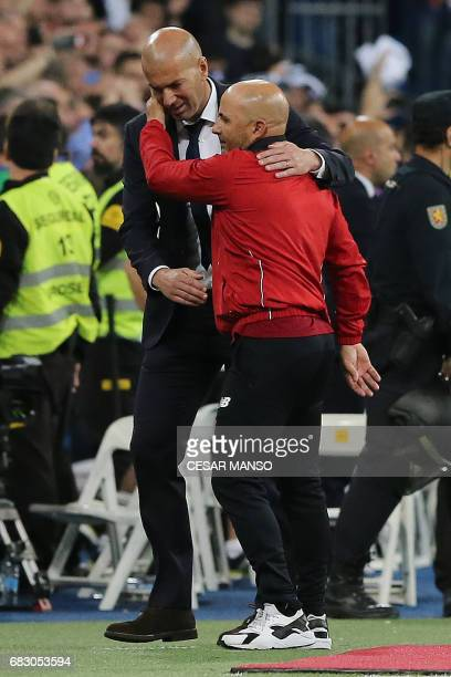 Real Madrid's French coach Zinedine Zidane cheers Sevilla's Argentinian coach Jorge Sampaoli after the Spanish league football match Real Madrid vs...