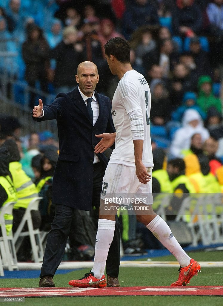 Real Madrid's French coach Zinedine Zidane (L) congratulates Real Madrid's French defender Raphael Varane as he leaves the pitch during the Spanish league football match Real Madrid CF vs Athletic Club Bilbao at the Santiago Bernabeu stadium in Madrid on February 13, 2016. / AFP / CURTO DE LA TORRE