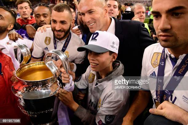 Real Madrid's French coach Zinedine Zidane his sons Elyaz and Enzo and Real Madrid's French striker Karim Benzema pose with the trophy after Real...
