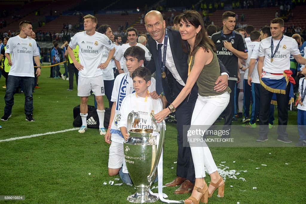 Real Madrid's French coach Zinedine Zidane (2nd L), his wife Veronique, and his sons Theo and Elyaz pose with the trophy after Real Madrid won the UEFA Champions League final football match between Real Madrid and Atletico Madrid at San Siro Stadium in Milan, on May 28, 2016. / AFP / Filippo MONTEFORTE