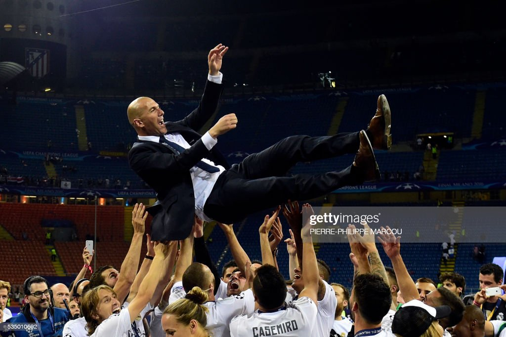 Real Madrid's French coach Zinedine Zidane is lifted by his players after Real Madrid won the UEFA Champions League final football match between Real Madrid and Atletico Madrid at San Siro Stadium in Milan, on May 28, 2016. / AFP / PIERRE