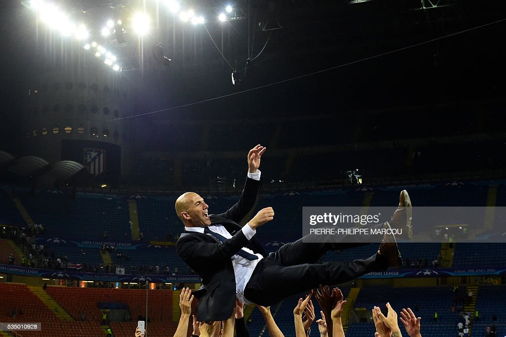 Real Madrid's French coach Zinedine Zidane is lifted by his players after Real Madrid won the UEFA Champions League final football match between Real Madrid and Atletico Madrid at San Siro Stadium in Milan, on May 28, 2016. Real Madrid beat city rivals Atletico for the second time in three years to win the Champions League for the 11th time on May 28. / AFP / PIERRE