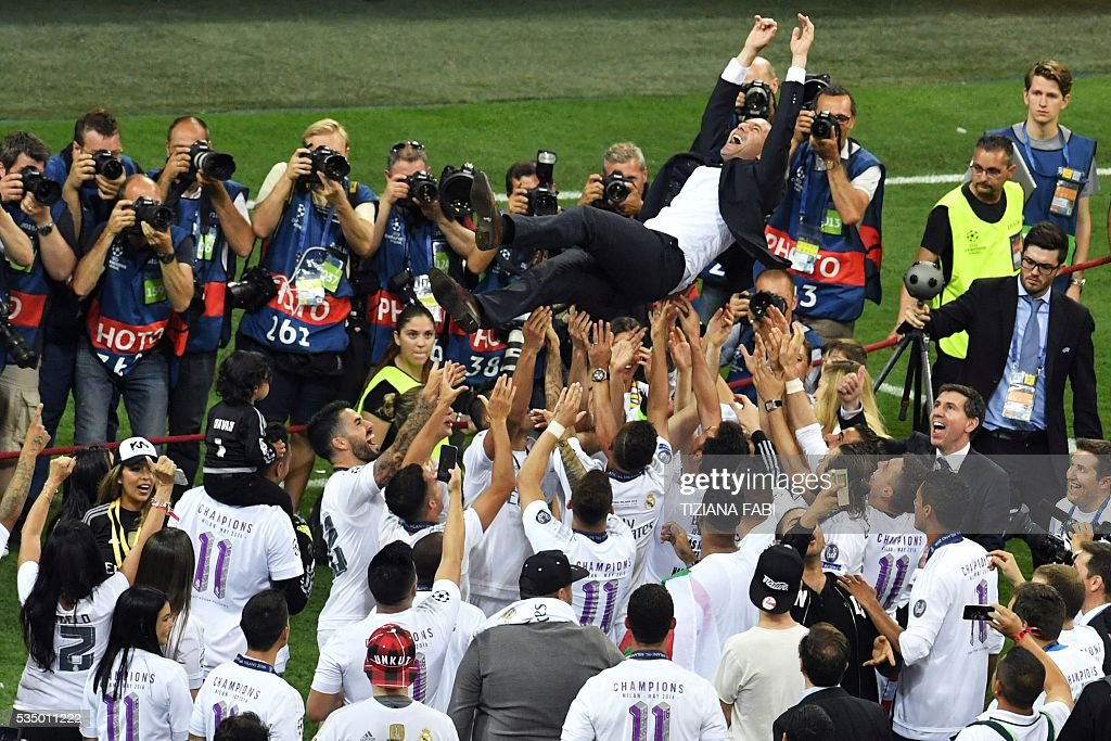 Real Madrid's French coach Zinedine Zidane is lifted by his players after Real Madrid won the UEFA Champions League final football match between Real Madrid and Atletico Madrid at San Siro Stadium in Milan on May 28, 2016. Real Madrid beat city rivals Atletico for the second time in three years to win the Champions League for the 11th time. / AFP / TIZIANA