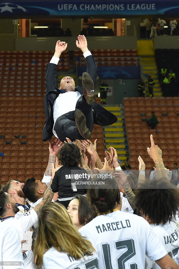 Real Madrid's French coach Zinedine Zidane is thrown into the air by Real Madrid players and staff members after they won the UEFA Champions League final football match over Atletico Madrid at San Siro Stadium in Milan, on May 28, 2016. / AFP / GERARD