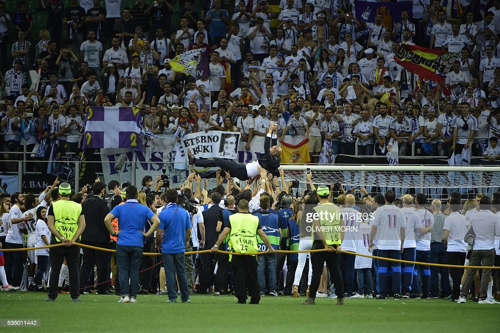 Real Madrid's French coach Zinedine Zidane is thrown into the air by Real Madrid players and staff members after they won the UEFA Champions League final football match over Atletico Madrid at San Siro Stadium in Milan, on May 28, 2016. / AFP / OLIVIER