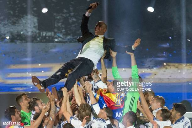 Real Madrid's French coach Zinedine Zidane is tossed by players as they celebrate the team's win at the Santiago Bernabeu stadium in Madrid on June 4...