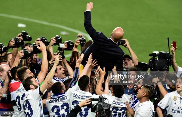 TOPSHOT Real Madrid's French coach Zinedine Zidane is tossed in the air by players as they celebrate winning the Liga title after the Spanish league...