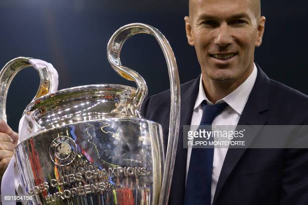 Real Madrid's French coach Zinedine Zidane lifts the trophy after Real Madrid won the UEFA Champions League final football match between Juventus and...