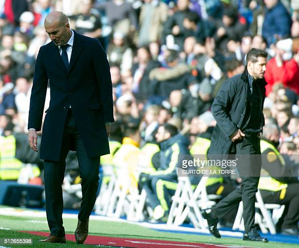 Real Madrid's French coach Zinedine Zidane looks down next to Atletico Madrid's Argentinian coach Diego Simeone during the Spanish league football...