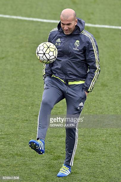Real Madrid's French coach Zinedine Zidane plays with a ball during a training session at Valdebebas training ground in Madrid on April 29 on the eve...
