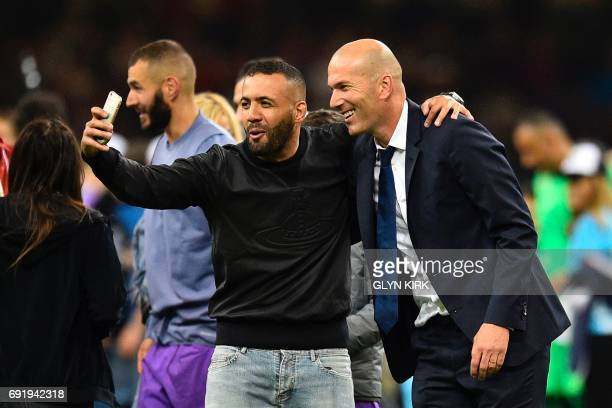Real Madrid's French coach Zinedine Zidane poses for a selfie during the UEFA Champions League final football match between Juventus and Real Madrid...