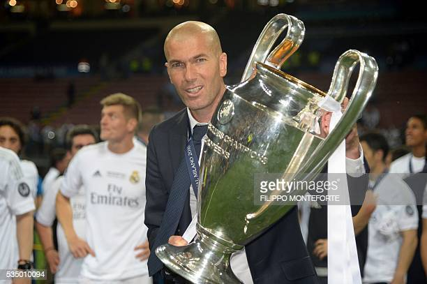 Real Madrid's French coach Zinedine Zidane poses with the trophy after Real Madrid won the UEFA Champions League final football match between Real...