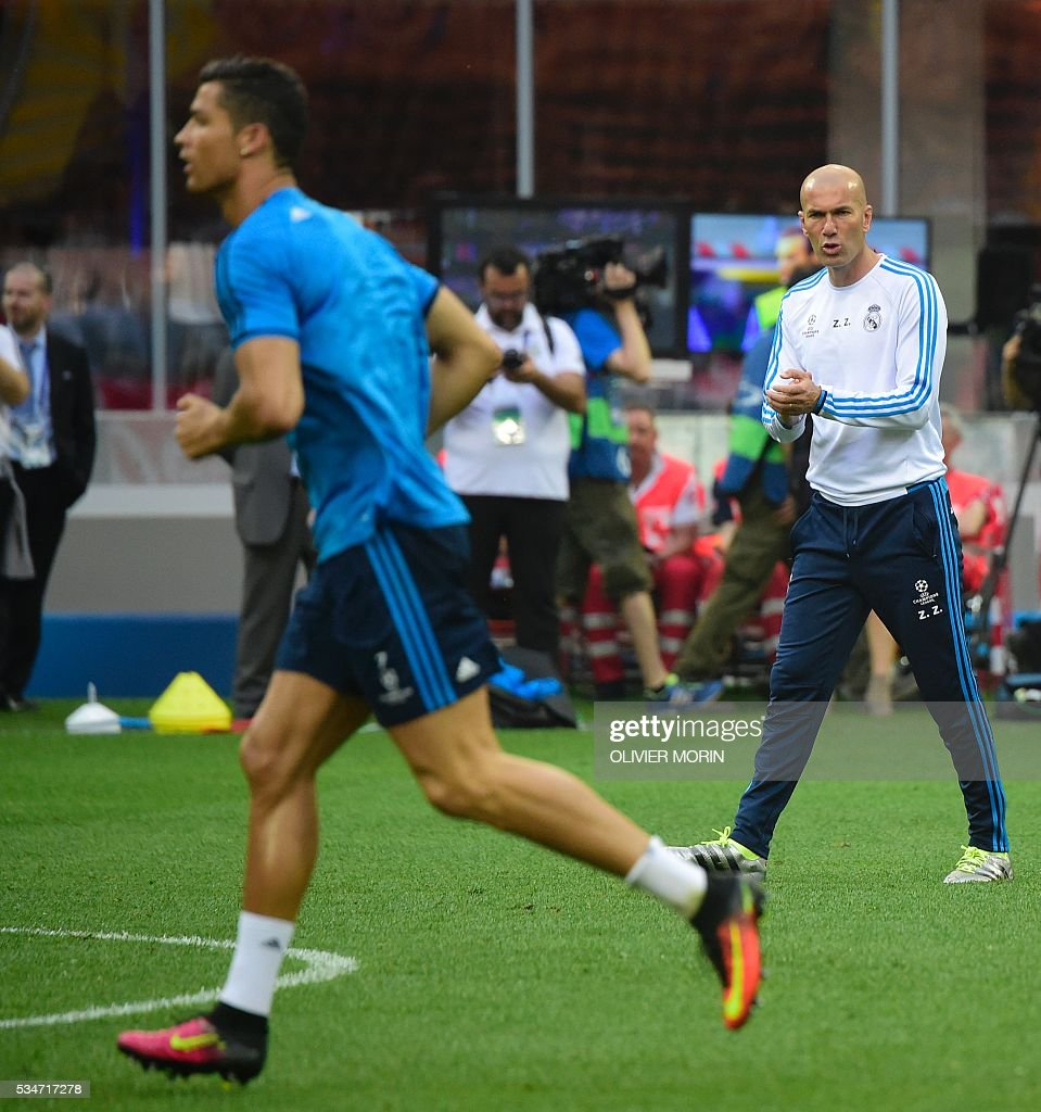 Real Madrid's French coach Zinedine Zidane (R) reacts next to Real Madrid's Portuguese forward Cristiano Ronaldo (L) during a training session at the San Siro Stadium in Milan, on May 27, 2016, on the eve of the UEFA Champions League final foobtall match between Real Madrid and Atletico Madrid. / AFP / OLIVIER