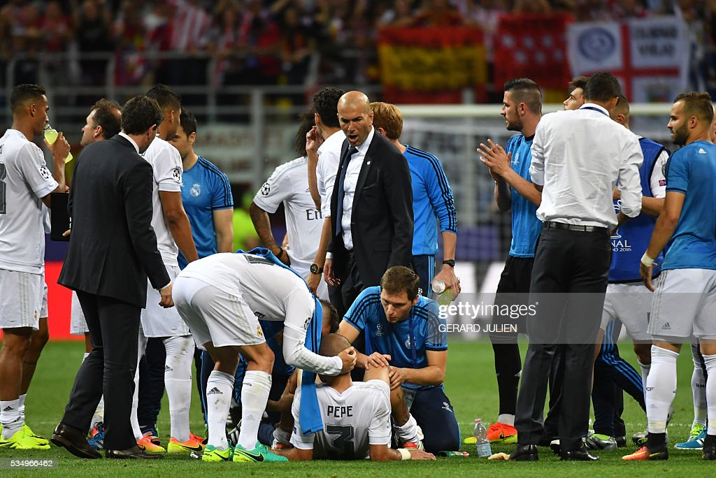 Real Madrid's French coach Zinedine Zidane (top, C) speaks with Real Madrid's Portuguese defender Pepe resting before extra-time during the UEFA Champions League final football match between Real Madrid and Atletico Madrid at San Siro Stadium in Milan, on May 28, 2016. / AFP / GERARD