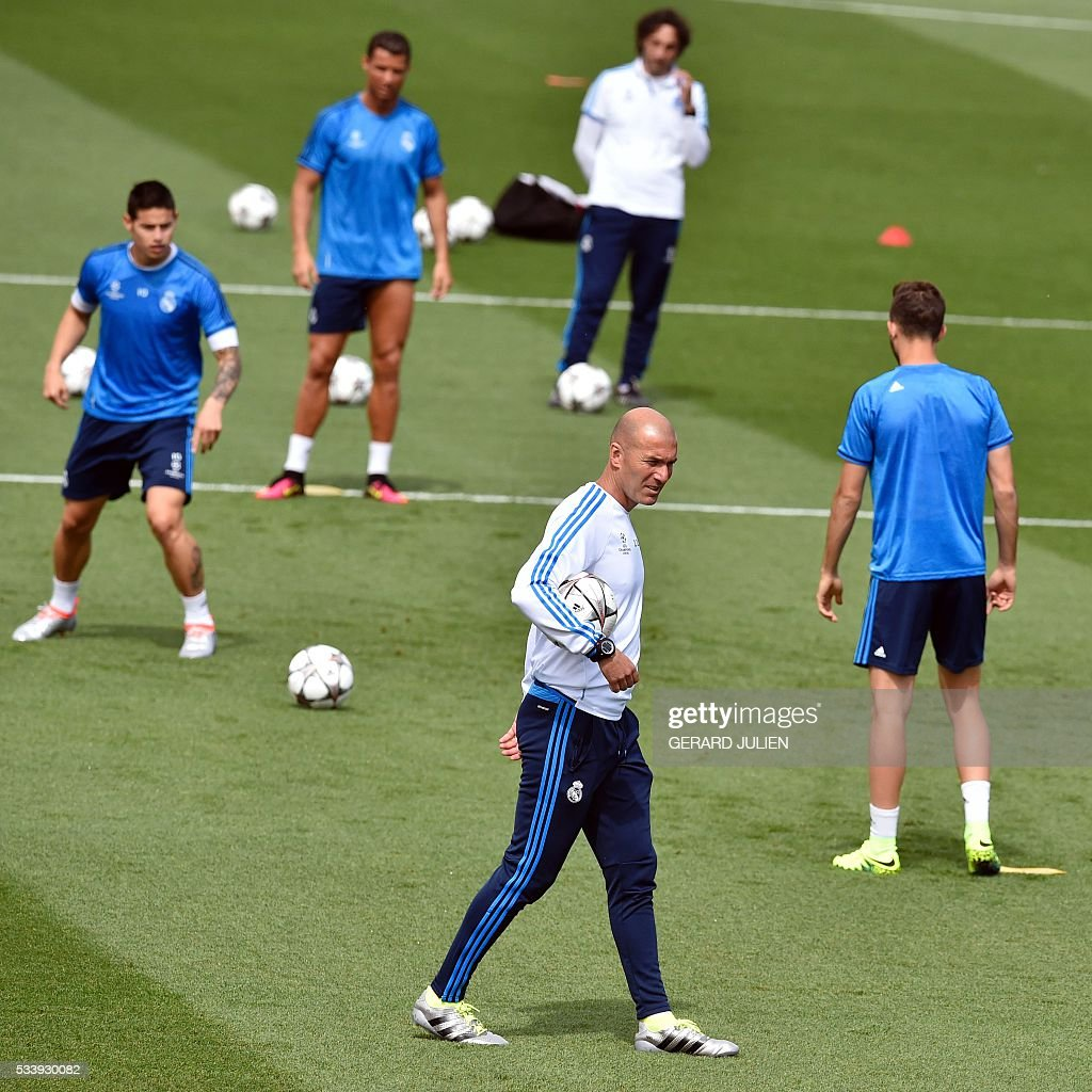 Real Madrid's French coach Zinedine Zidane (C) walks on the pitch during a training session on the club's Open Media Day at Real Madrid sport city in Madrid on May 24, 2016. / AFP / GERARD