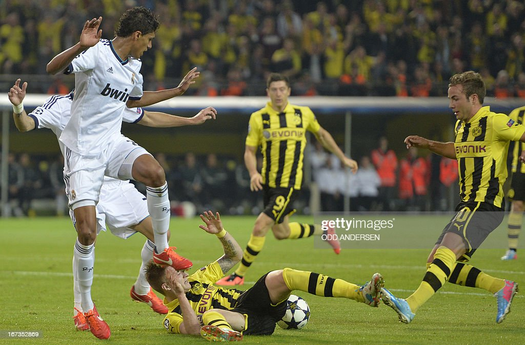 Real Madrid's French defender Raphael Varane (L) catches Dortmund's striker Marco Reus (bottom) with his foot during the UEFA Champions League semi final first leg football match between Borussia Dortmund and Real Madrid on April 24, 2013 in Dortmund, western Germany. AFP PHOTO / ODD ANDERSEN
