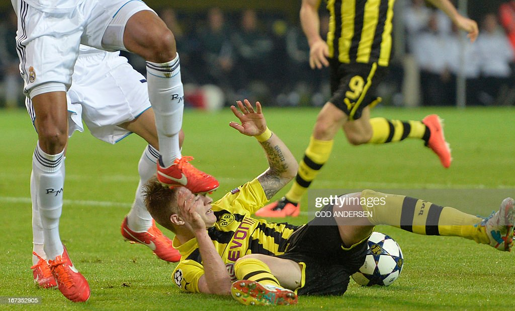 Real Madrid's French defender Raphael Varane (L) catches Dortmund's striker Marco Reus (bottom) with his foot during the UEFA Champions League semi final first leg football match between Borussia Dortmund and Real Madrid on April 24, 2013 in Dortmund, western Germany.