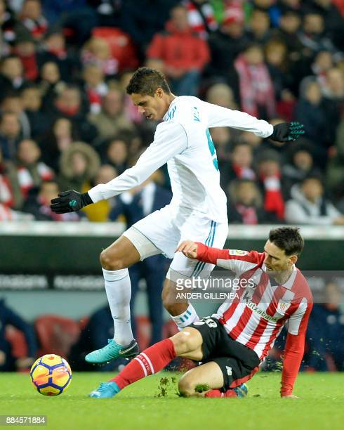 Real Madrid's French defender Raphael Varane challenges Athletic Bilbao's Spanish forward Aritz Aduriz during the Spanish league football match...