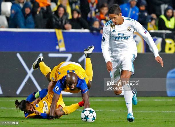Real Madrid's French defender Raphael Varane dribbles with the ball as Apoel's Cypriot midfielder Efstathios Aloneftis colides with Apoel's Beninese...