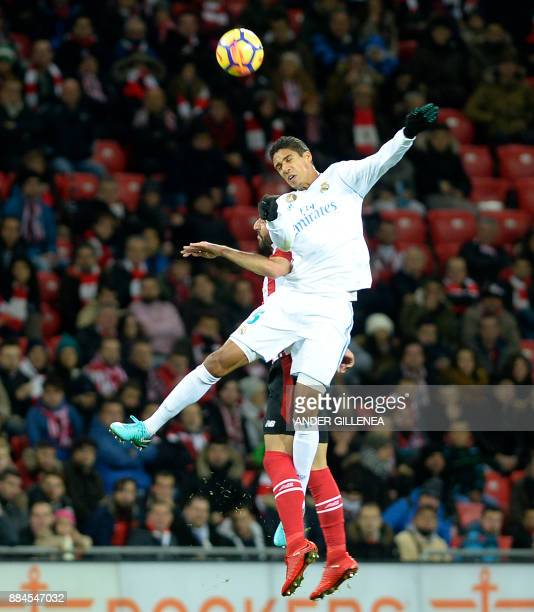 Real Madrid's French defender Raphael Varane heads the ball with Athletic Bilbao's Spanish midfielder Raul Garcia during the Spanish league football...