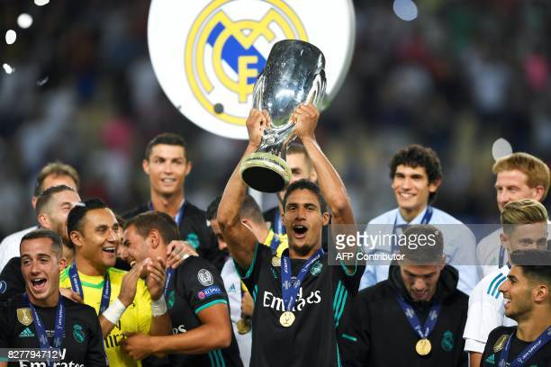 Real Madrid's French defender Raphael Varane holds the trophy after winning the UEFA Super Cup football match between Real Madrid and Manchester...