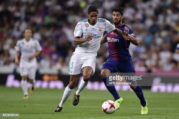 Real Madrid's French defender Raphael Varane vies with Barcelona's Uruguayan forward Luis Suarez during the second leg of the Spanish Supercup...