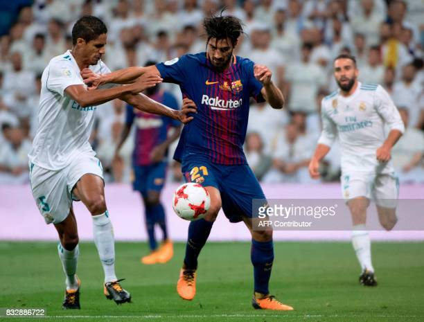 Real Madrid's French defender Raphael Varane vies with Barcelona's Portuguese midfielder Andre Gomes during the second leg of the Spanish Supercup...
