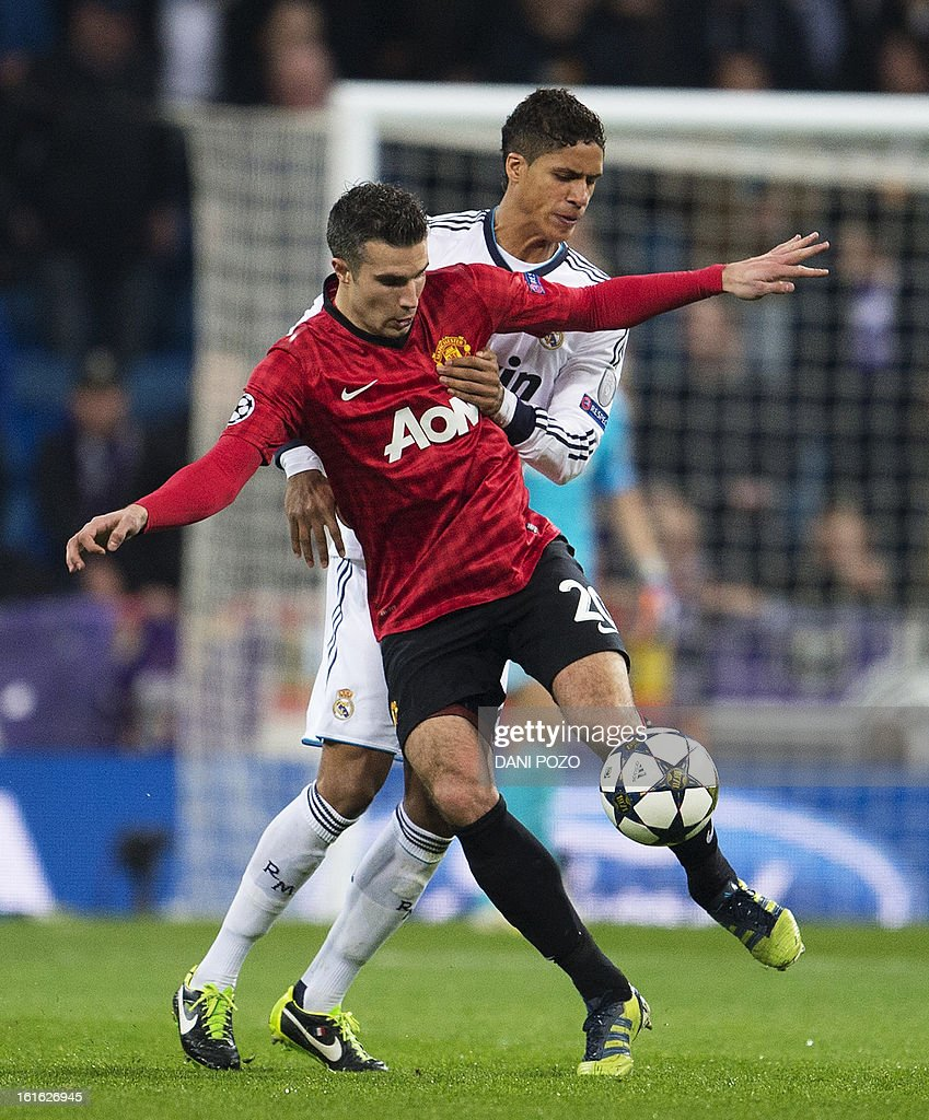 Real Madrid's French defender Raphael Varane (back) vies with Manchester United's Dutch striker Robin van Persie during the UEFA Champions League round of 16 first leg football match Real Madrid CF vs Manchester United FC at the Santiago Bernabeu stadium in Madrid on February 13, 2013. AFP PHOTO/ DANI POZO