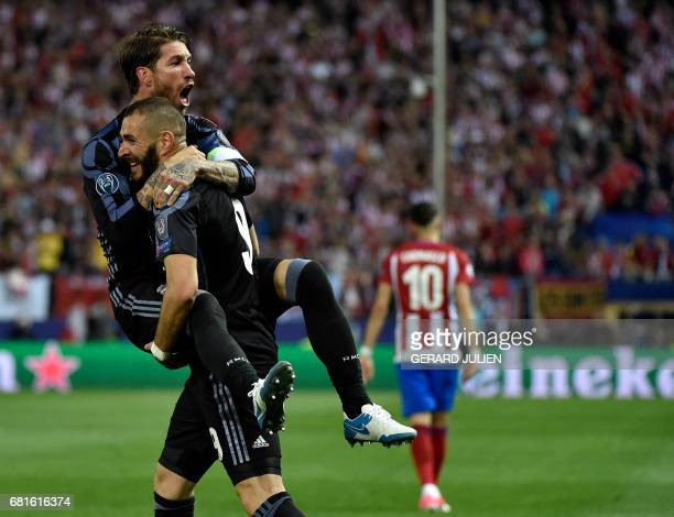 TOPSHOT Real Madrid's French forward Karim Benzema and Real Madrid's defender Sergio Ramos celebrate their opening goal during the UEFA Champions...