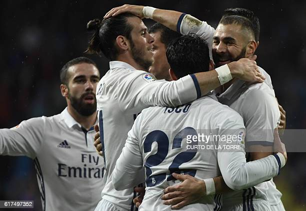 Real Madrid's French forward Karim Benzema celebrates a goal with teammates during the Spanish league football match between Real Madrid CF and...