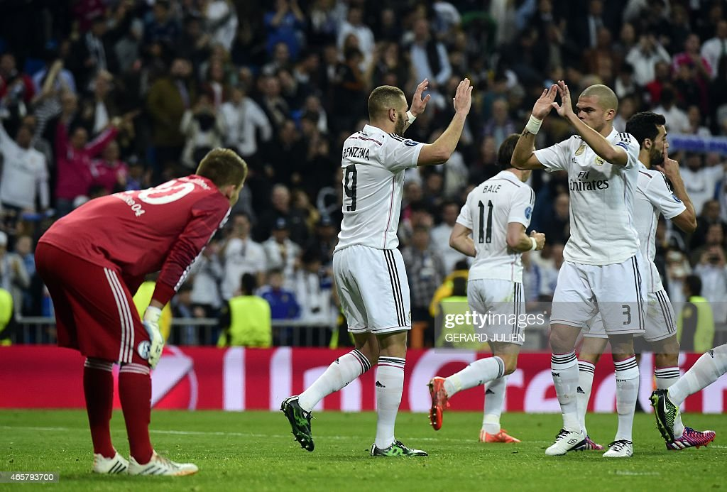 Real Madrid's French forward <a gi-track='captionPersonalityLinkClicked' href=/galleries/search?phrase=Karim+Benzema&family=editorial&specificpeople=796089 ng-click='$event.stopPropagation()'>Karim Benzema</a> (C) celebrates after scoring with Real Madrid's Portuguese defender <a gi-track='captionPersonalityLinkClicked' href=/galleries/search?phrase=Pepe+-+Portuguese+Soccer+Player&family=editorial&specificpeople=4401229 ng-click='$event.stopPropagation()'>Pepe</a> and next to Schalke's goalkeeper <a gi-track='captionPersonalityLinkClicked' href=/galleries/search?phrase=Timon+Wellenreuther&family=editorial&specificpeople=12550527 ng-click='$event.stopPropagation()'>Timon Wellenreuther</a> (L) during the UEFA Champions League round of 16 second leg football match Real Madrid CF vs FC Schalke 04 at the Santiago Bernabeu stadium in Madrid on March 10, 2015.