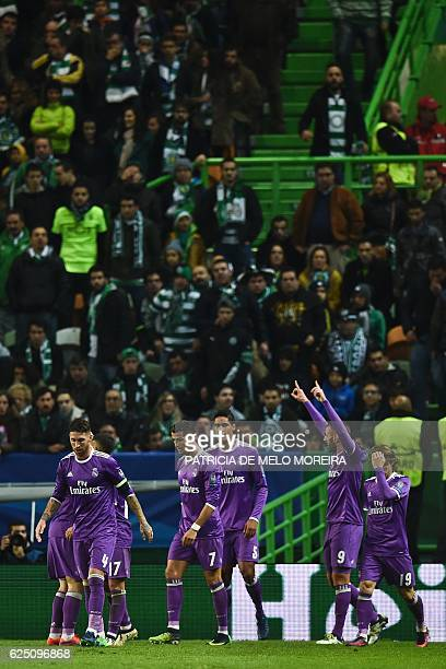 Real Madrid's French forward Karim Benzema celebrates with his teammates after scoring a goal during the UEFA Champions League football match...