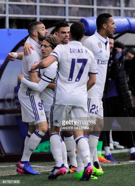 Real Madrid's French forward Karim Benzema celebrates with Real Madrid's Croatian midfielder Luka Modric and teammates after scoring their team's...