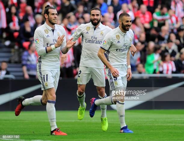 Real Madrid's French forward Karim Benzema celebrates with teammates Welsh forward Gareth Bale and defender Daniel Carvajal after scoring their...