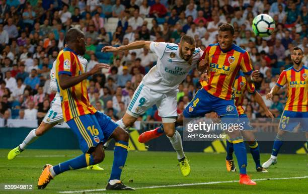 TOPSHOT Real Madrid's French forward Karim Benzema heads the ball past Valencia's Brazilian defender Jeison Murillo during the Spanish league...