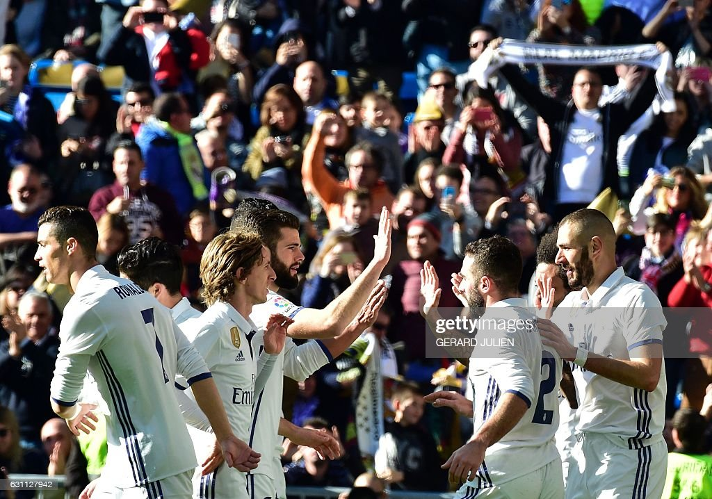 Real Madrid's French forward Karim Benzema (R) is congratulated by his teammates after scoring during the Spanish league football match Real Madrid CF vs Granada FC at the Santiago Bernabeu stadium in Madrid on January 7, 2017. / AFP / GERARD