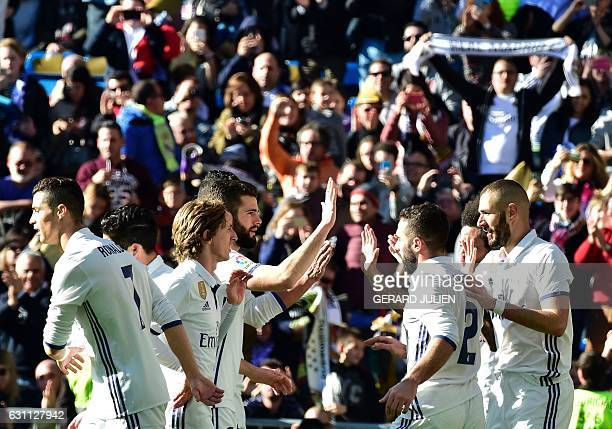 Real Madrid's French forward Karim Benzema is congratulated by his teammates after scoring during the Spanish league football match Real Madrid CF vs...
